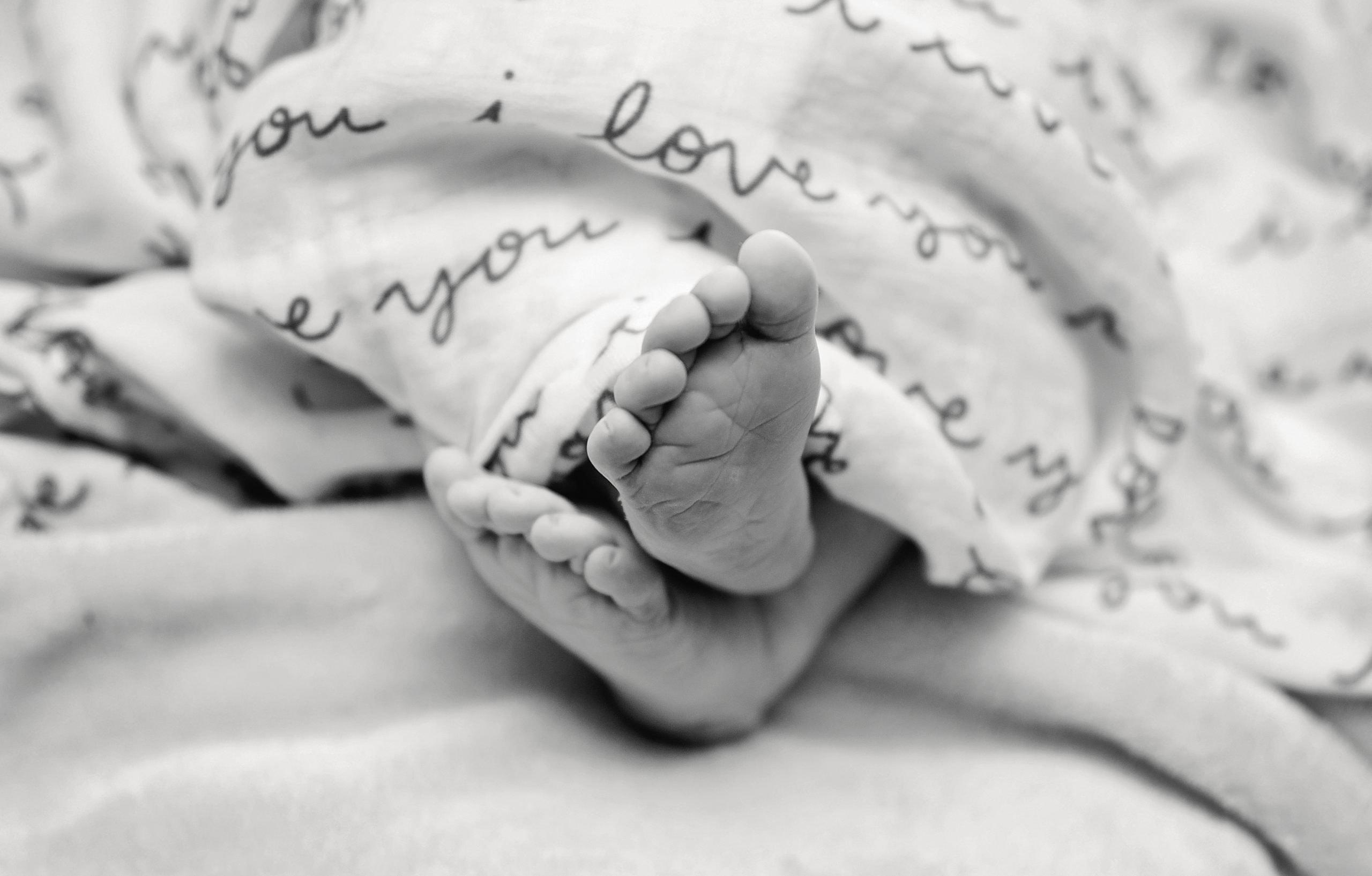 Baby feet under a blanket.