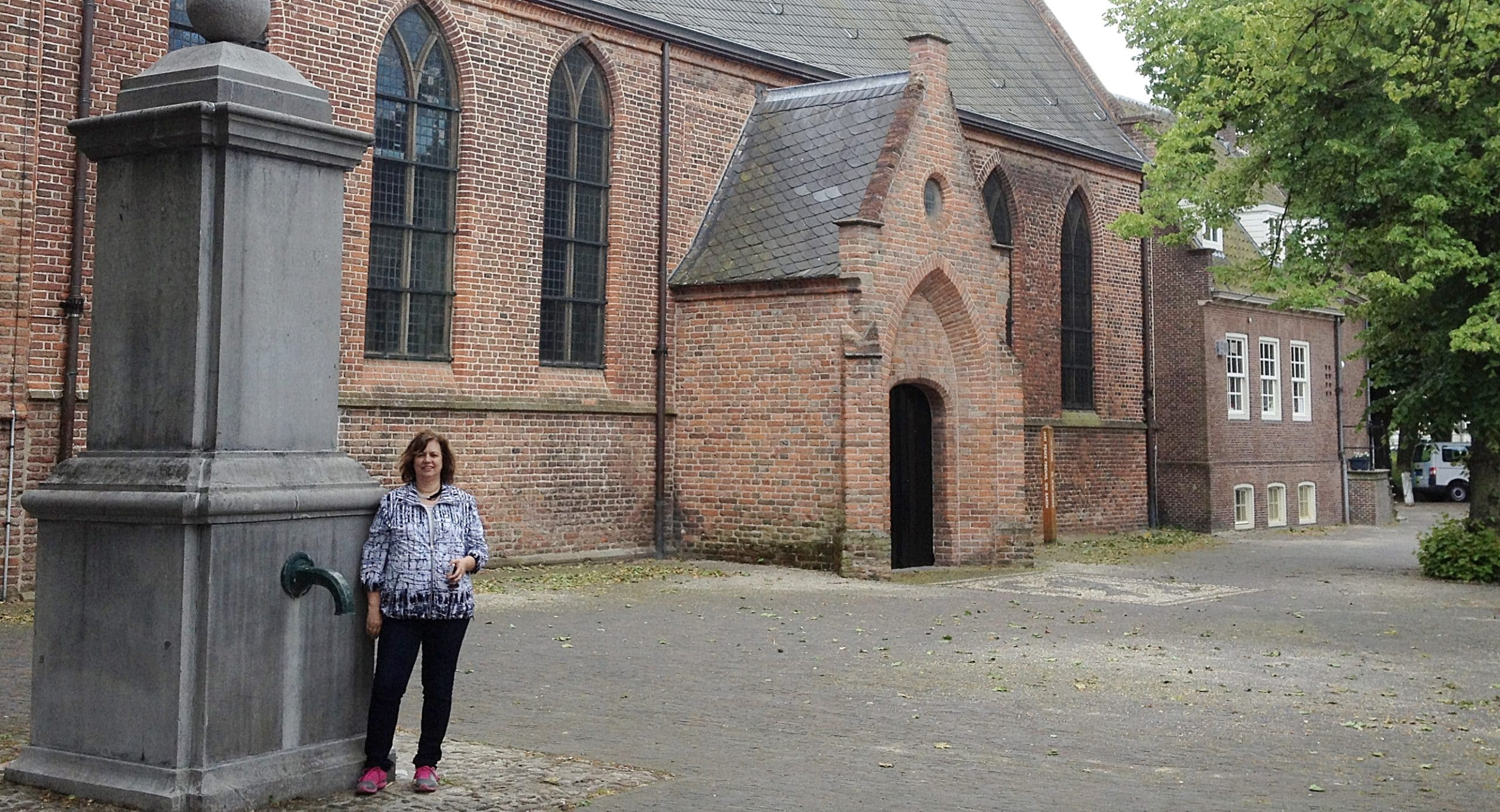A woman standing outside of a brick church.