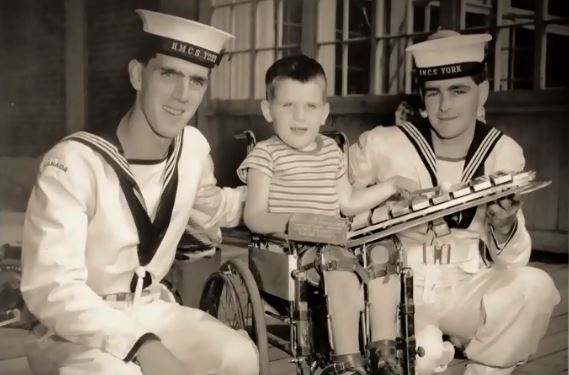 a boy in between two older boys in sailor clothes