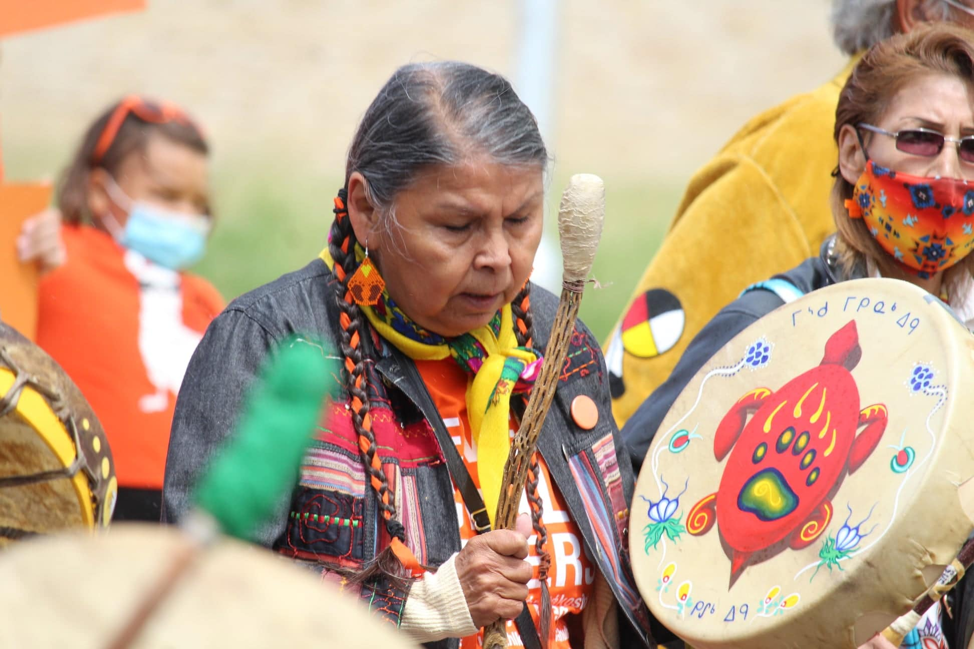 a woman beating a drum