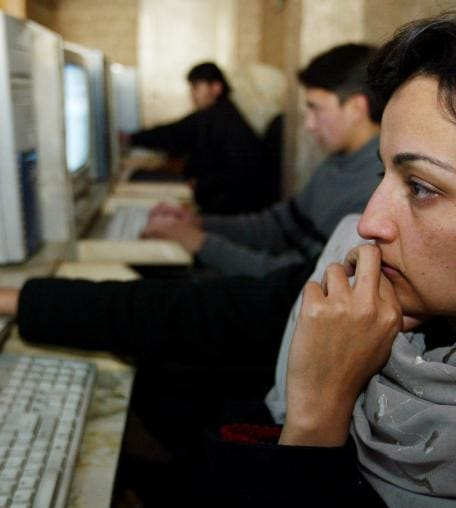 An Afghan woman uses a computer at the Park Residence Internet Cafe in Kabul, Afghanistan.
