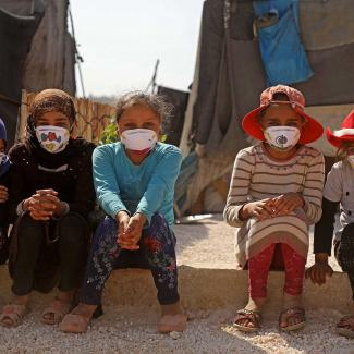 Displaced Syrian girls wear face masks decorated by artists during a COVID-19 awareness campaign at the Bardaqli camp in Syria's Idlib province, on April 20, 2020.