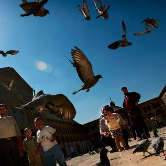 Pigeons fly after being fed by Syrians in the courtyard of the Omayad mosque October 18, 2002 in Damascus, Syria.
