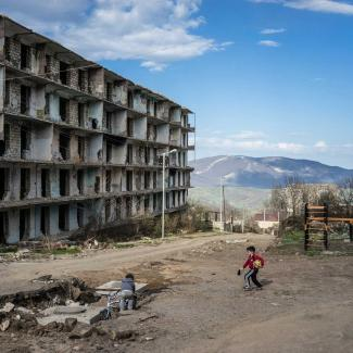 Boys play on a street next to a building destroyed by war more than twenty years earlier on April 18, 2015 in Shushi, Nagorno-Karabakh.
