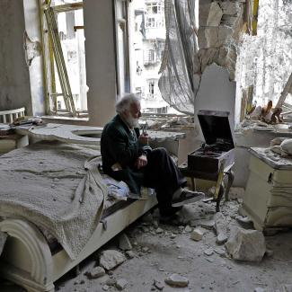 Abu Omar, 70, sits in his destroyed bedroom listening to music on his record player, in Aleppo's al-Shaar neighbourhood.