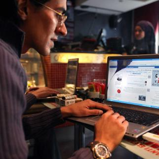 A man looks at a laptop computer displaying Facebook in a cafe on January 27, 2011 as anti government protesters take to the streets in Cairo, Egypt.