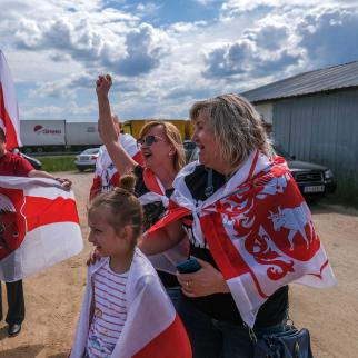 Exiled Belarusians hold historical Belarus opposition flags as they take part in a protest at the Polish-Belarusian border crossing on June 05, 2021 in Bobrowniki, Poland.