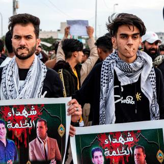 """Protesters wearing bandages crossing their mouths stand holding up signs showing the faces of two slain journalists captioned in Arabic """"martyrs of the word"""" during an anti-government demonstration, also calling for freedom of the press, in the southern Iraqi city of Basra on January 17, 2020."""