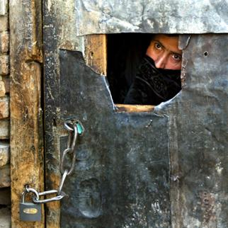 A female inmate peers out the front door as she waits to be released from the women's prison in Kabul. (Photo: Paula Bronstein/Getty Images)