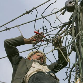 Electric power lines are vulnerable to sabotage and failure. (Photo: Paula Bronstein/Getty Images) An electrician works on power lines in Kabul. (Photo: Paula Bronstein/Getty Images)