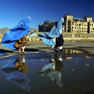 Women in burqas walk in front of the ruins of Darulaman Palace in Kabul. (Photo: Paula Bronstein/Getty Images)
