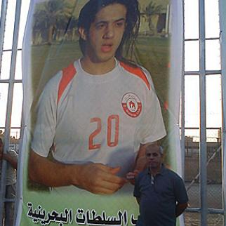 Father of detained footballer Zulfiqar Naji standing next to a poster of his son. (Photo: Hanadi Naji)