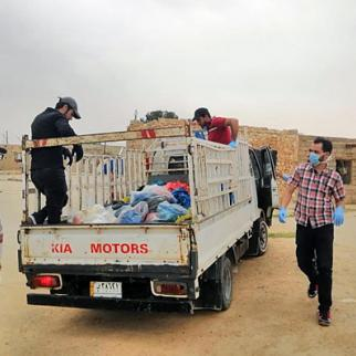 Iraqi activists distribute donation over poor families in Akour area in Anbar province. (Photo: IWPR)