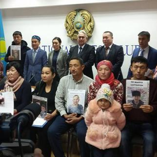 Ethnic Kazaks from China with pictures of their disappeared relatives in Xinjang region. (Photo courtesy of Bureau.kz)