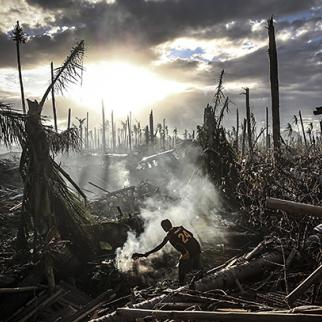 A man fans flames on a fire in Tanauan on November 19, 2013 in Leyte, Philippines. (Photo: Dan Kitwood/copyright Getty Images)