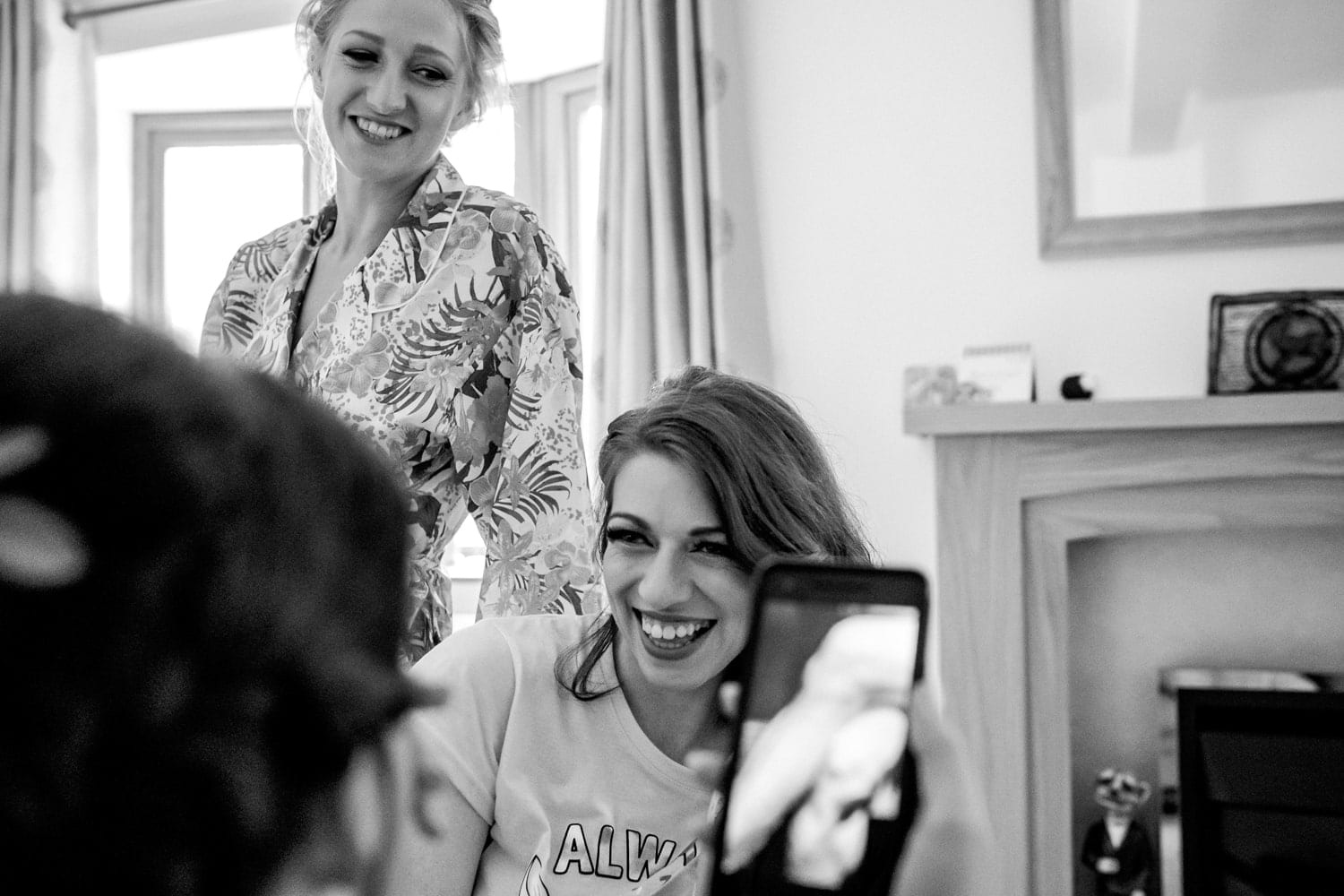 bride and bridesmaids laughing whist getitng ready
