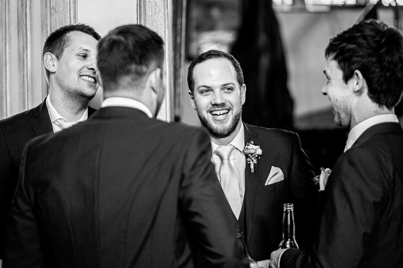 the groom laughing with his groomsmen