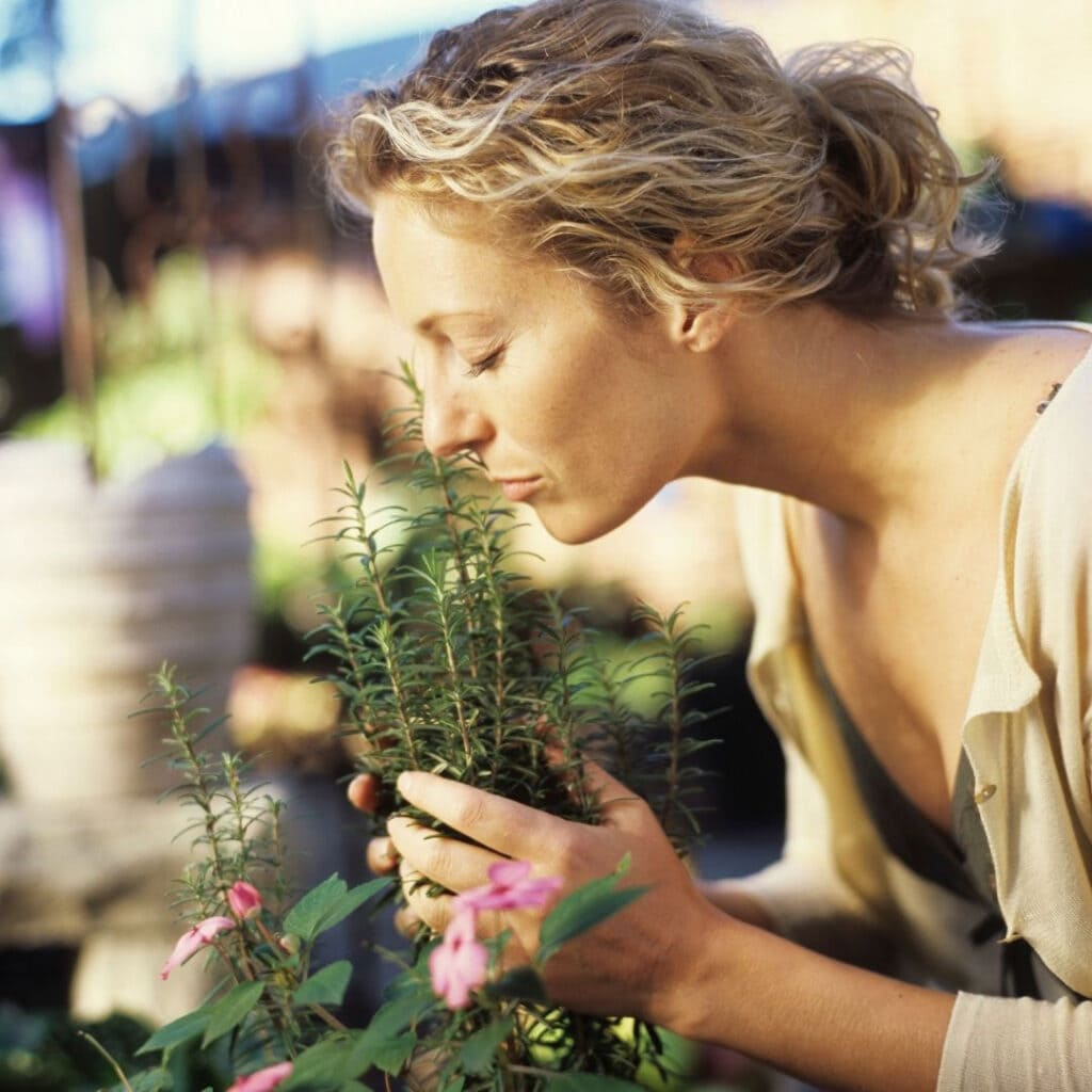 Woman inhaling the scent of rosemary