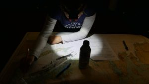 Emily studying sailing charts by head lamp