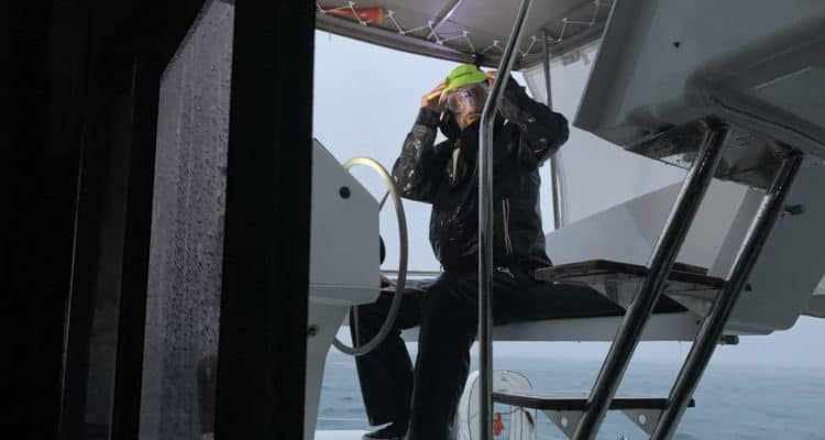 Matt at the helm of Sea Odyssey with goggles on looking scared in 60 knots of wind