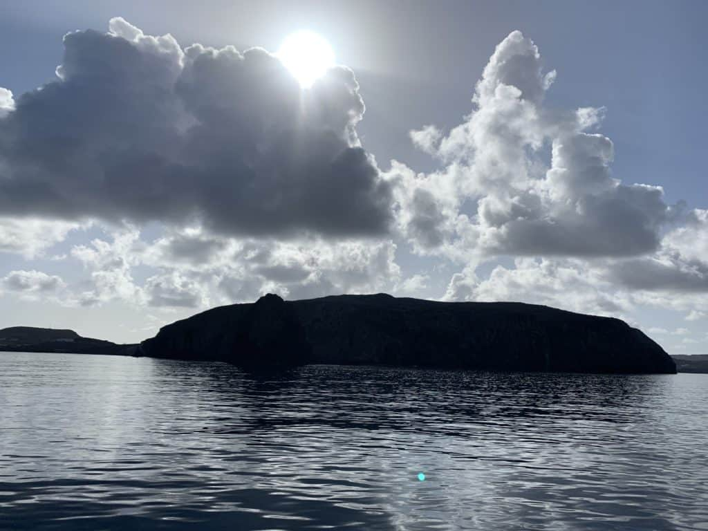 island with sun behind clouds