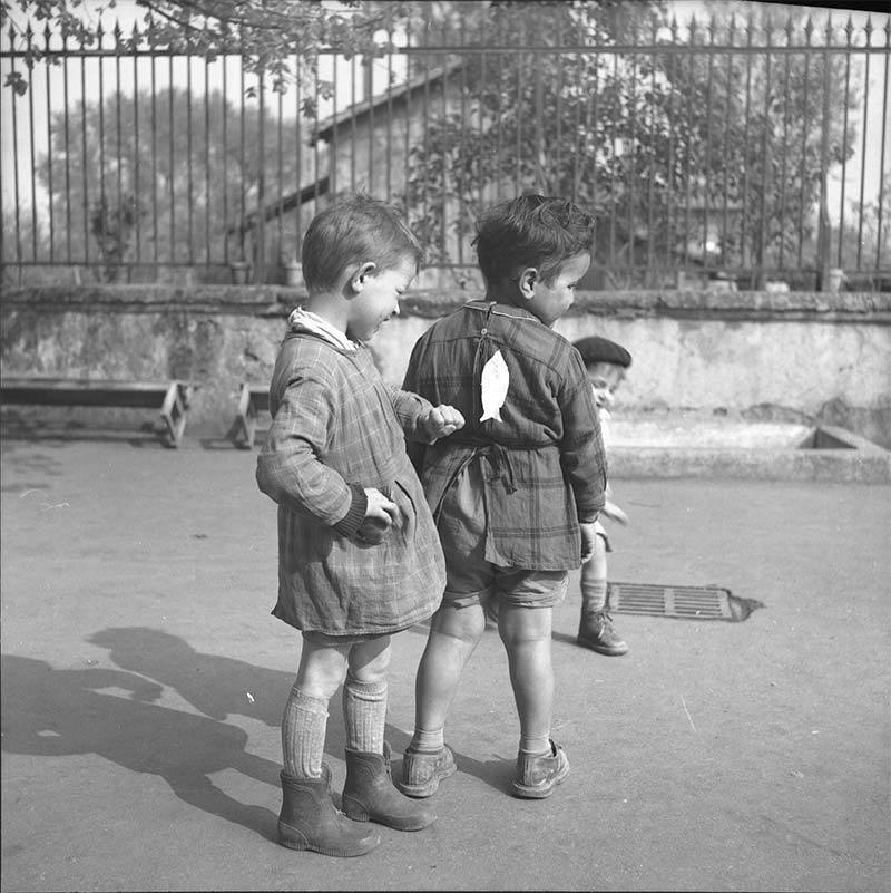 Photo of French school boy putting paper fish on back of his friend