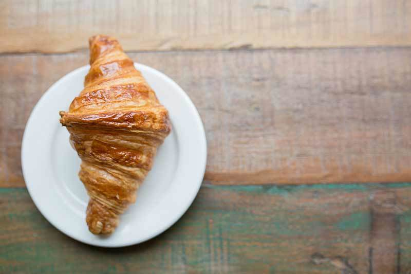 photo of a lone croissant on a plate