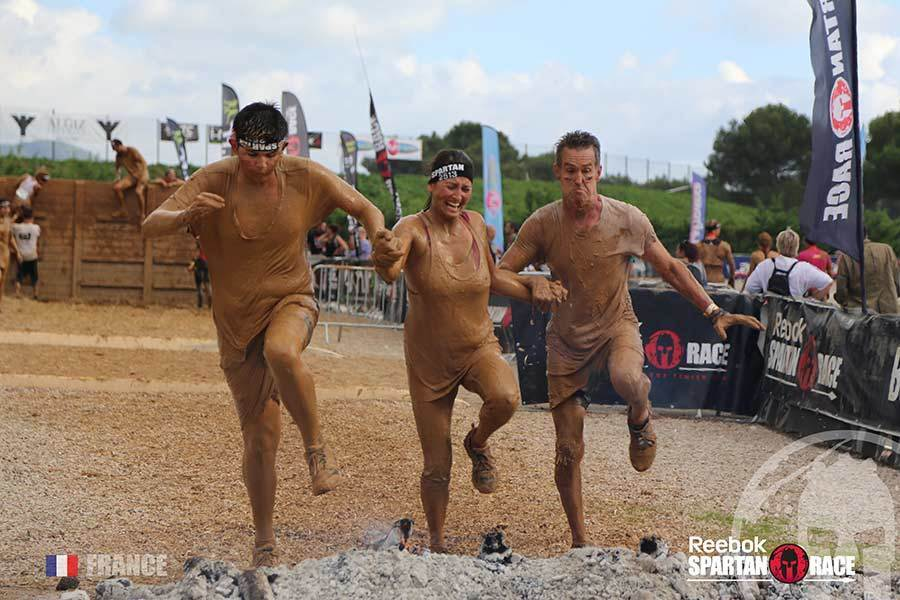 Annie Andre with my husband and son at the Spartan Race in Castellet France about to jump over the fire pit