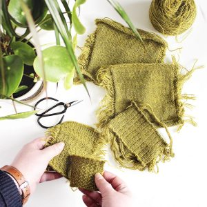 hands holding two green knitted swatches. more swatches lie on a white table in the background, along with houseplants and a pair of black scissors