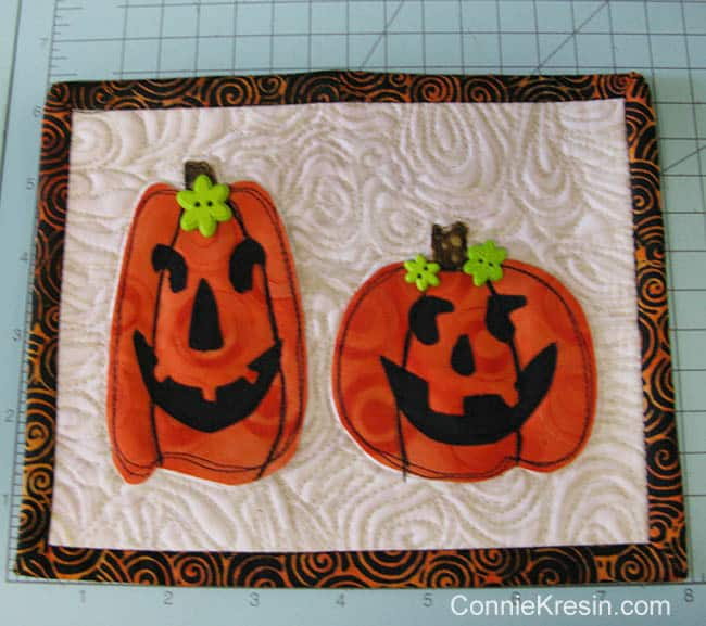 Two pumpkins mug rug finished with green buttons