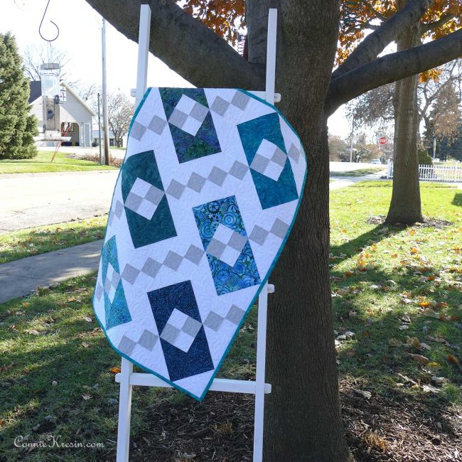 Jacob's Ladder Box quilt hanging on a ladder by the tree