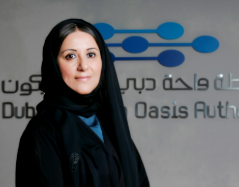 Shahla Abdulrazak deputy SEO of DSO wearing a black abaya, smiling, standing infront of a wall with a DSOA logo