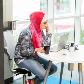 Female wearing a red and white headscarf sitting at a Dtec flexi-desk working on a laptop