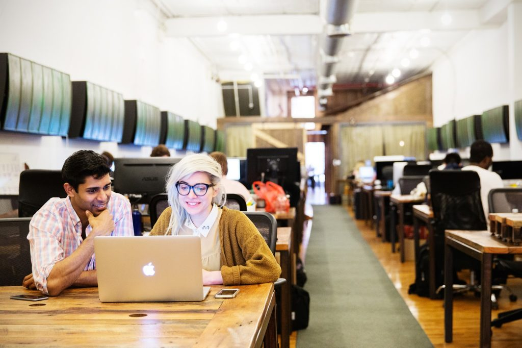 Man and woman with laptop in a Coworking space