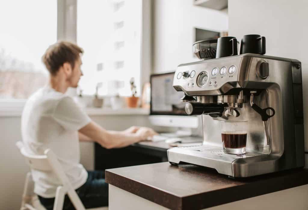 Bild zeigt eine Sieträgermaschine rechts im Vordergrund mit einem Glas Espresso unter dem Auslauf. Im Hintergrund ist ein junger Mann zu sehen, der auf einem weißen Klappstuhl sitzt und auf den Bildschirm eines Mac auf seinem Schreibtisch schaut.