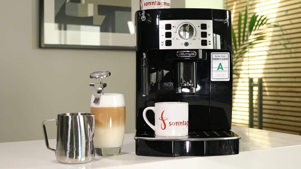 DeLonghi Magnifica S ECAM 22.110.B Kaffeevollautomat mit Edelstahl-Milchkännchen und einem gefüllten hohen Glas mit Latte Macchiato links daneben stehend