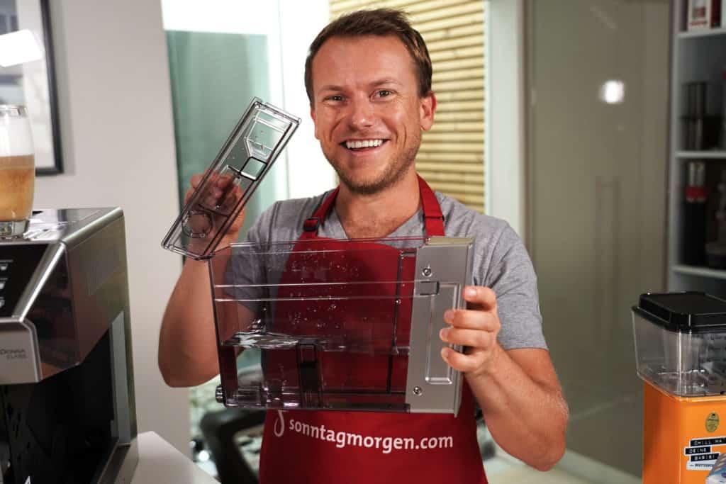 Wassertank des DeLonghi PrimaDonna Class Kaffeevollautomaten wird von Arne von Sonntagmorgen hochgehalten, der Deckel in der rechten Hand