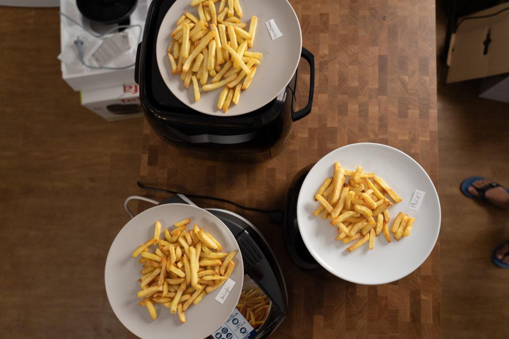 Pommes-Ergebnisse: drei Teller mit fertig zubereiteten Pommes aus verschiedenen Airfryern aus der Vogelperspektive