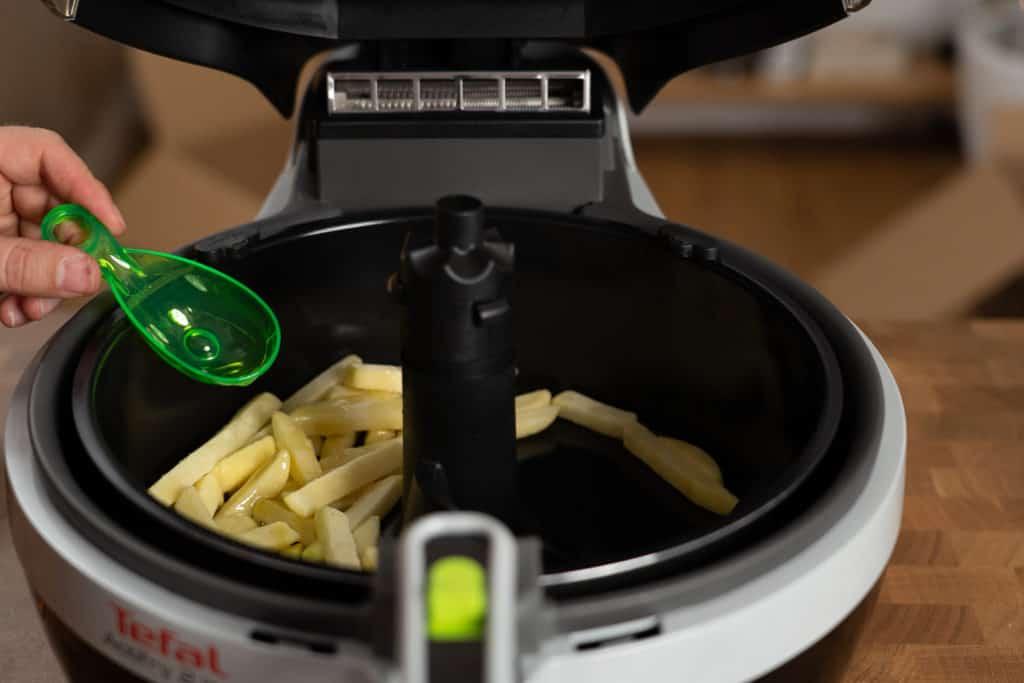Tefal ActiFry 2in1 YV9601 Heißluftfritteuse - Gerät ist geöffnet und Tiefkühlpommes werden mit etwas Öl vor der Zubereitung beträufelt