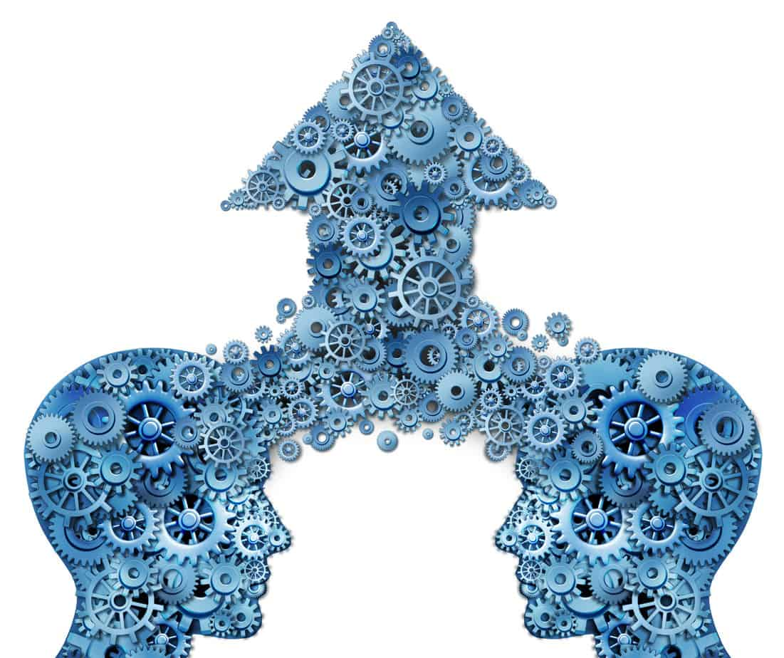 Corporate partnership and business teamwork growth concept with two human head shapes merging together to form an upward pointing arrow made of gears and cogs as a financial success symbol on a white background.