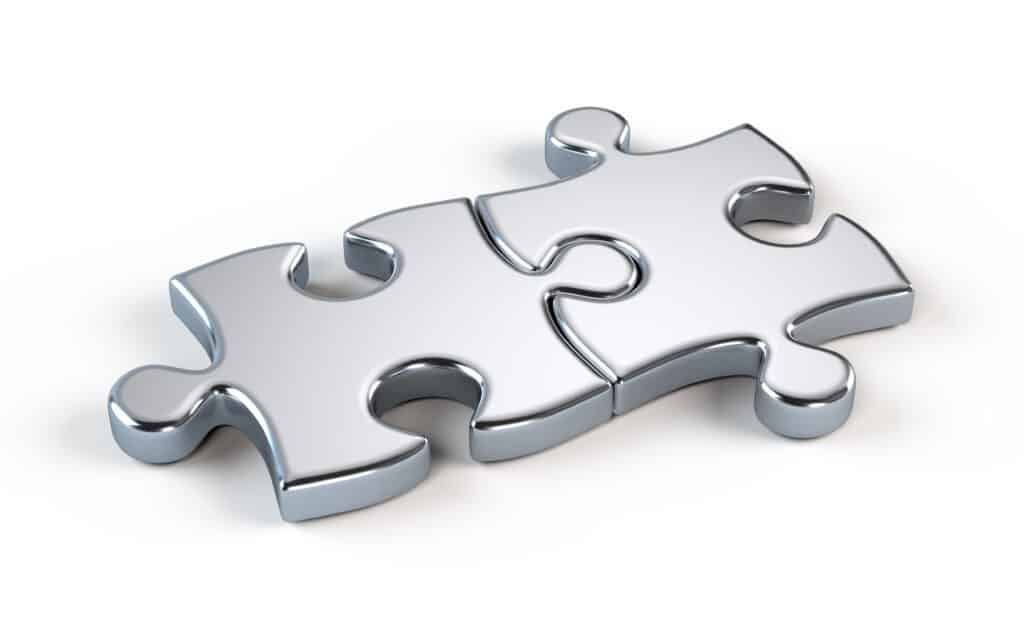 Two metal jigsaw puzzle pieces attached to each other.