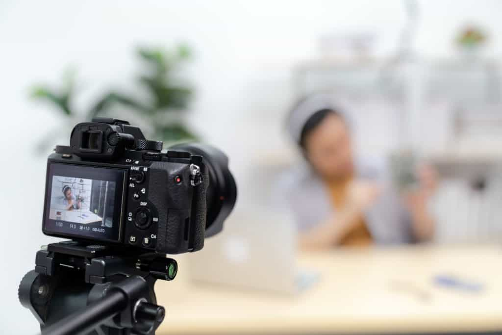 Camera pointed at a vlogger/blogger recording a video with the focus on the camera