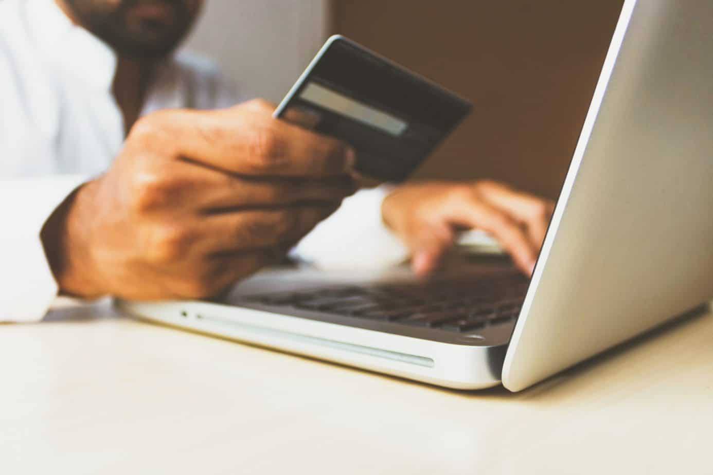 A man with credit card in his hand in front of a open laptop