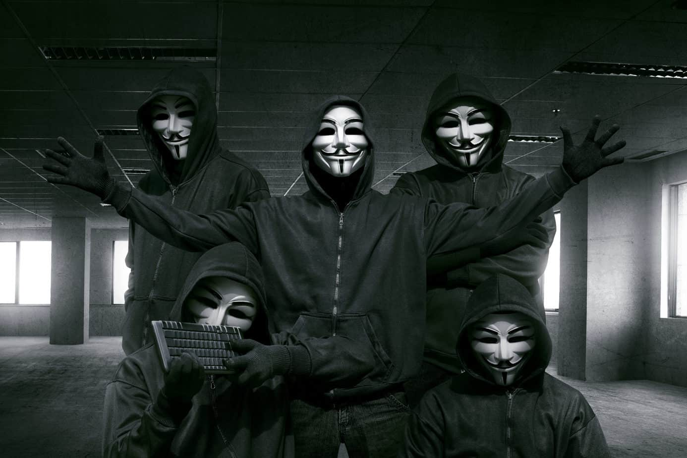 Group of hooded hacker with mask standing in the dark room background
