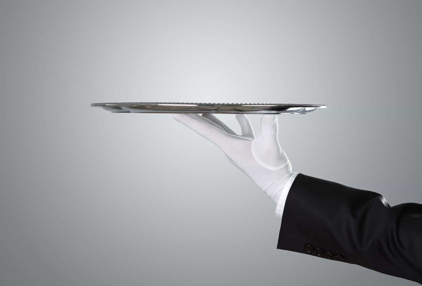 A butlers arm wearing a white glove holding a silver platter