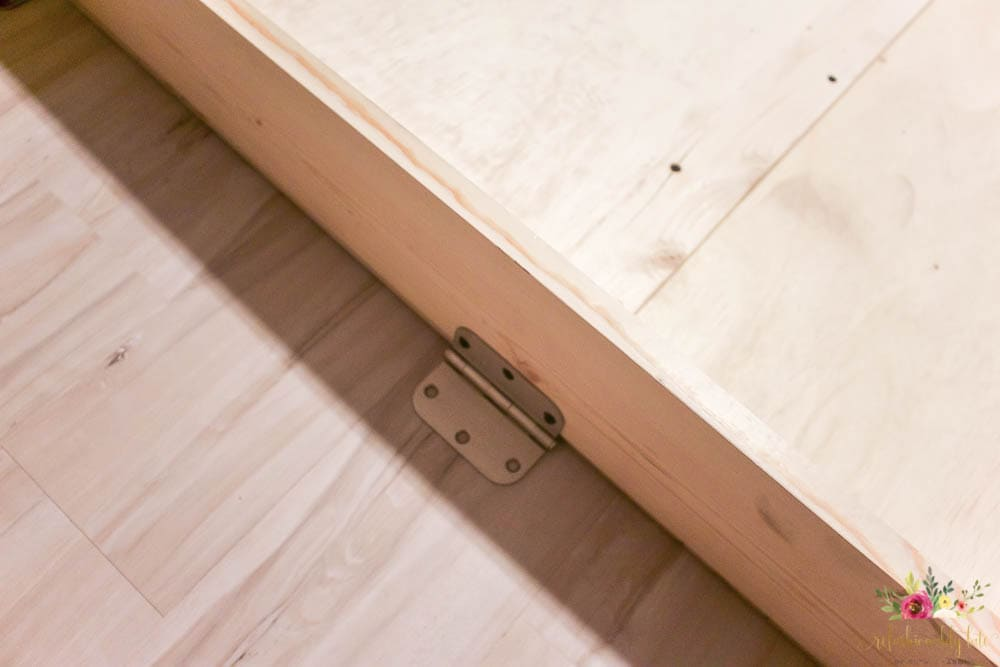 bed frame laying on a vinyl floor with door hinge attached to it
