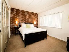 Bedroom of an apartment with brick wall inside the Allenway