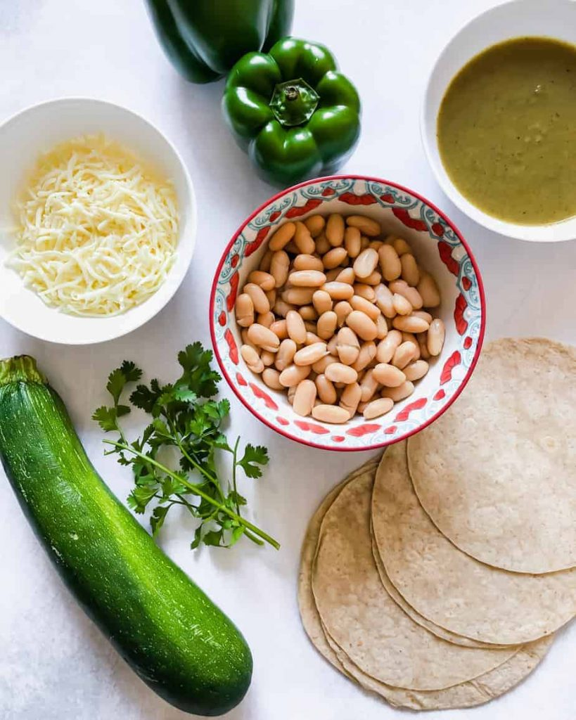 ingredients in bowls and on marble slab: zucchini, cilantro, shredded cheese, green pepper, white beans, enchilada sauce, tortillas