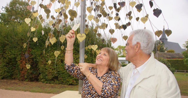 A French couple posing at the tree of hearts in Saint-Valentin. They renewed their wedding vows