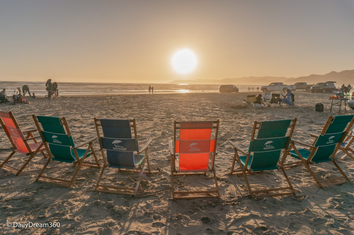 Beach chairs facing sunset at Oceano Dunes State Park